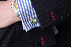 Closeup showing a cuff-link through a shirt.
