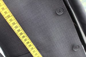 A yellow measuring tape laid across a grey tailored suit.